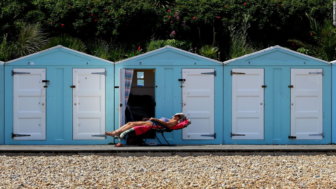 A woman enjoys the sunshine outside her beach hut in Eastbourne, England, on Sunday, June 19.