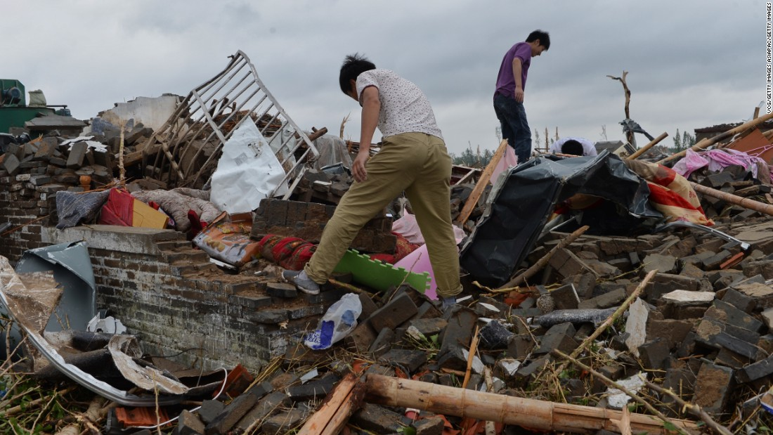 Funing residents search for belongings in the rubble of collapsed houses on June 24.