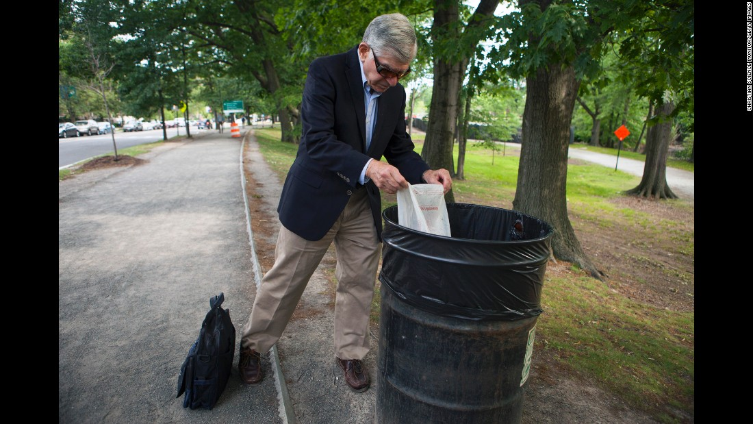 Michael Dukakis, the former Massachusetts governor who ran for President in 1988, empties a plastic bag that he filled with trash during his 2-mile walk to work on Wednesday, June 22. Dukakis is now a professor at Northeastern University in Boston, and he has long been an advocate for the environment.