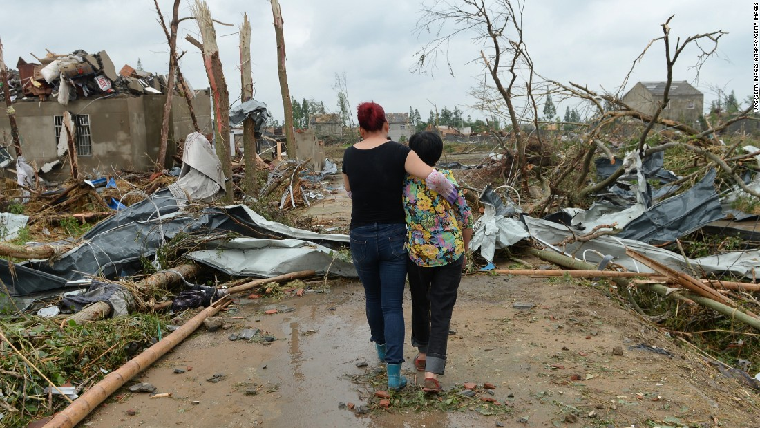 One woman supports another as they pass through the rubble of collapsed houses in Funing on June 24.