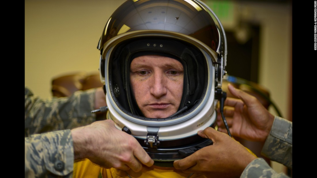 Airmen fasten a helmet onto Air Force Lt. Col. Todd Larsen on Thursday, June 16. Those who pilot U-2 reconnaissance aircraft have to wear pressurized suits to compensate for a lack of atmosphere at ultra-high altitudes.
