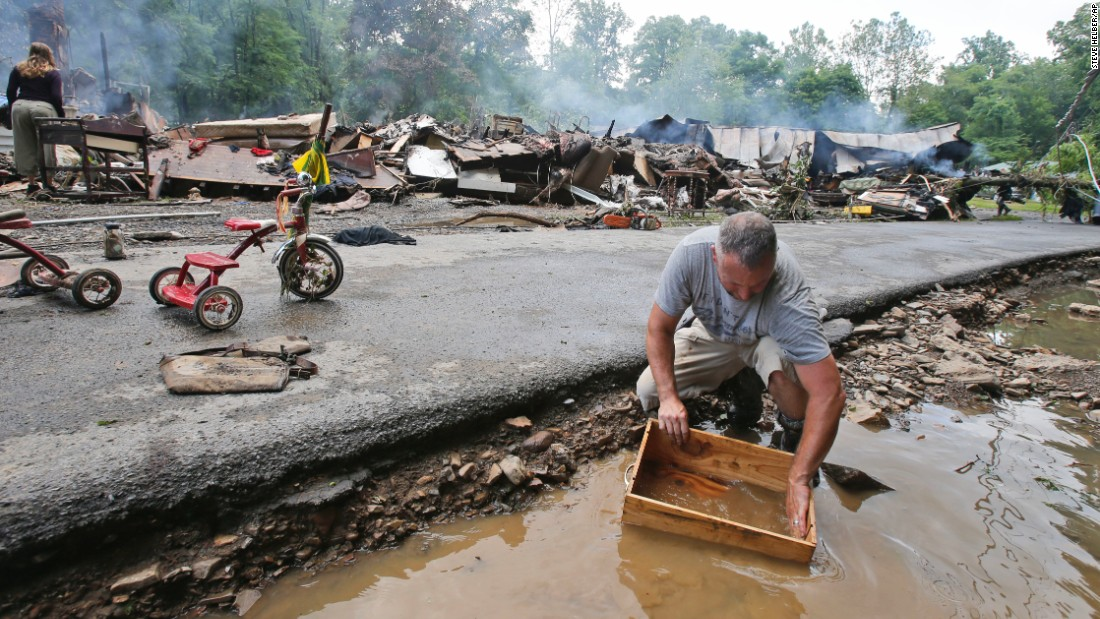 Mark Lester cleans out a box with creek water as he cleans up in White Sulphur Springs on June 24.