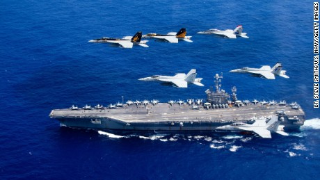 In this handout provided by the U.S. Navy, a combined formation of aircraft from Carrier Air Wing (CVW) 5 and Carrier Air Wing (CVW) 9 pass in formation above the Nimitz-class aircraft carrier USS John C. Stennis (CVN 74). The formation included F/A-18 Hornets from the Black Aces of Strike Fighter Squadron 41, the Diamondbacks of Strike Fighter Squadron 102, the Eagles of Strike Fighter Squadron 115, the Royal Maces of Strike Fighter Squadron 27, the Vigilantes of Strike Fighter Squadron 151, and the Warhawks of Strike Fighter Squadron 97. The Nimitz-class aircraft carriers USS John C. Stennis and USS Ronald Reagan (CVN 76) are conducting dual aircraft carrier strike group operations in the U.S. 7th Fleet area of operations in support of security and stability in the Indo-Asia-Pacific.