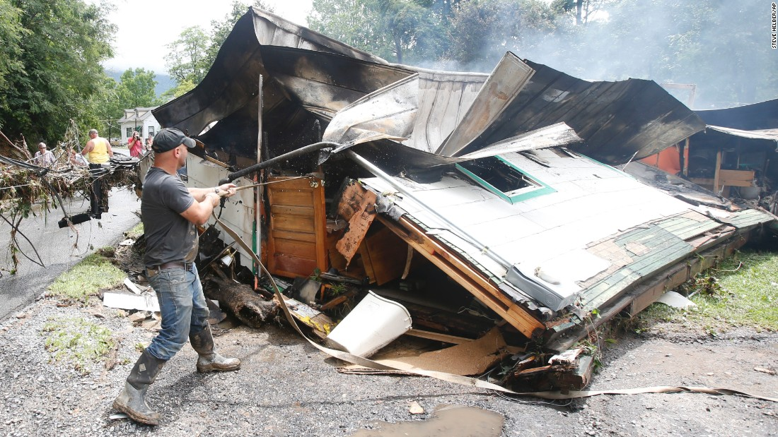 Lee Bland looks for belongings in the burned-out home of a relative as they clean up from severe flooding in White Sulphur Springs on June 24.