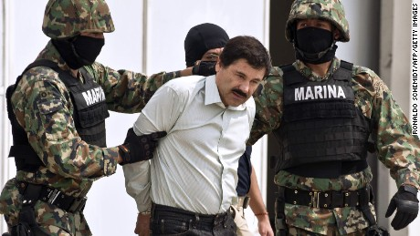 Guzman is escorted by marines as he is presented to the press on February 22, 2014 in Mexico City.