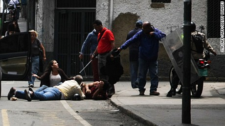 Security forces hold journalists lying on the street during a demonstration against the severe food and medicine shortages in Venezuela, heading to Miraflores presidential palace in Caracas on June 2, 2016. Venezuelans face long lines at supermarkets tightly guarded by nervous soldiers, bare shelves and soaring prices inside, a dysfunctional health care system short on basic medications and supplies, daily power cuts of four hours across most of the country, and a government that only operates two days a week to save electricity. / AFP / STR        (Photo credit should read STR/AFP/Getty Images)