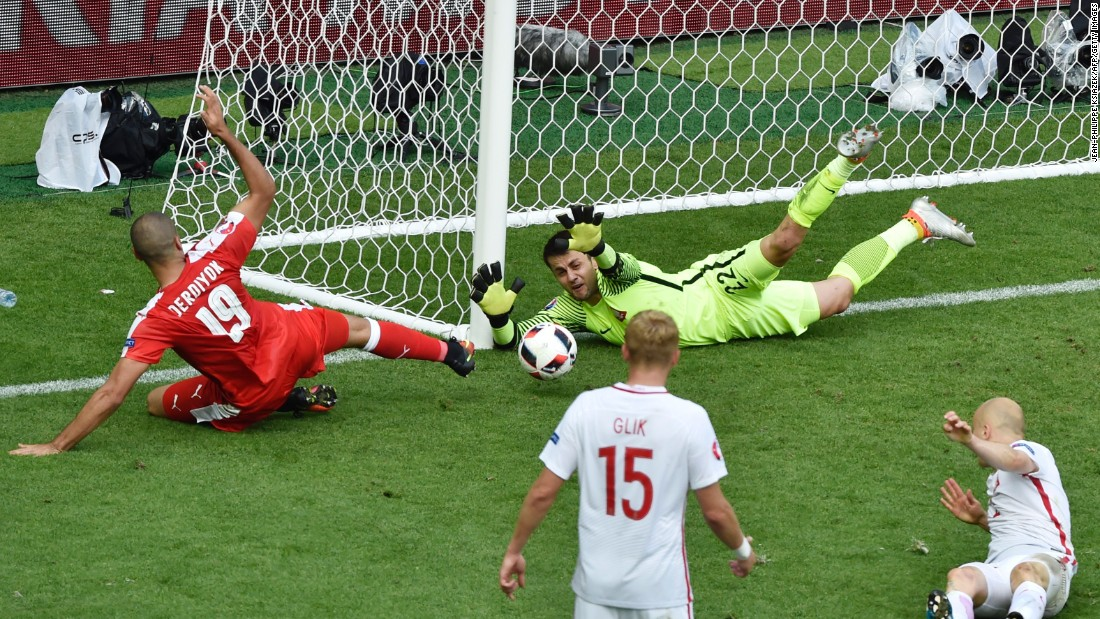 Poland goalkeeper Lukasz Fabianski, top right, saves an attempt by Switzerland forward Eren Derdiyok, left.