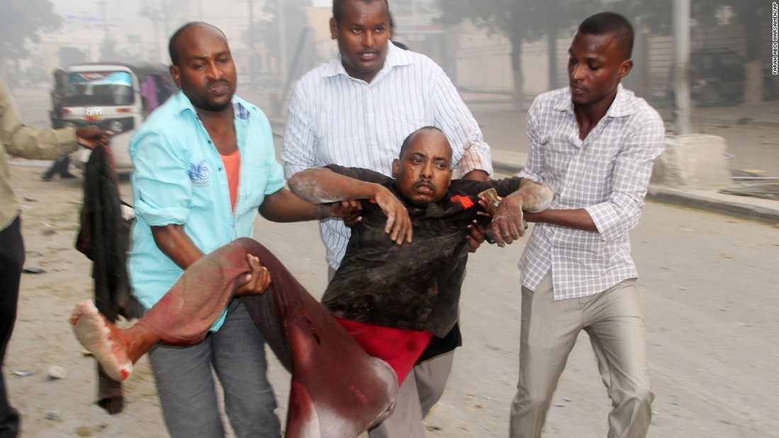 Somali men help a wounded civilian. Most of those killed and injured were civilians who were passersby and customers of nearby shops and the gas station, police said.
