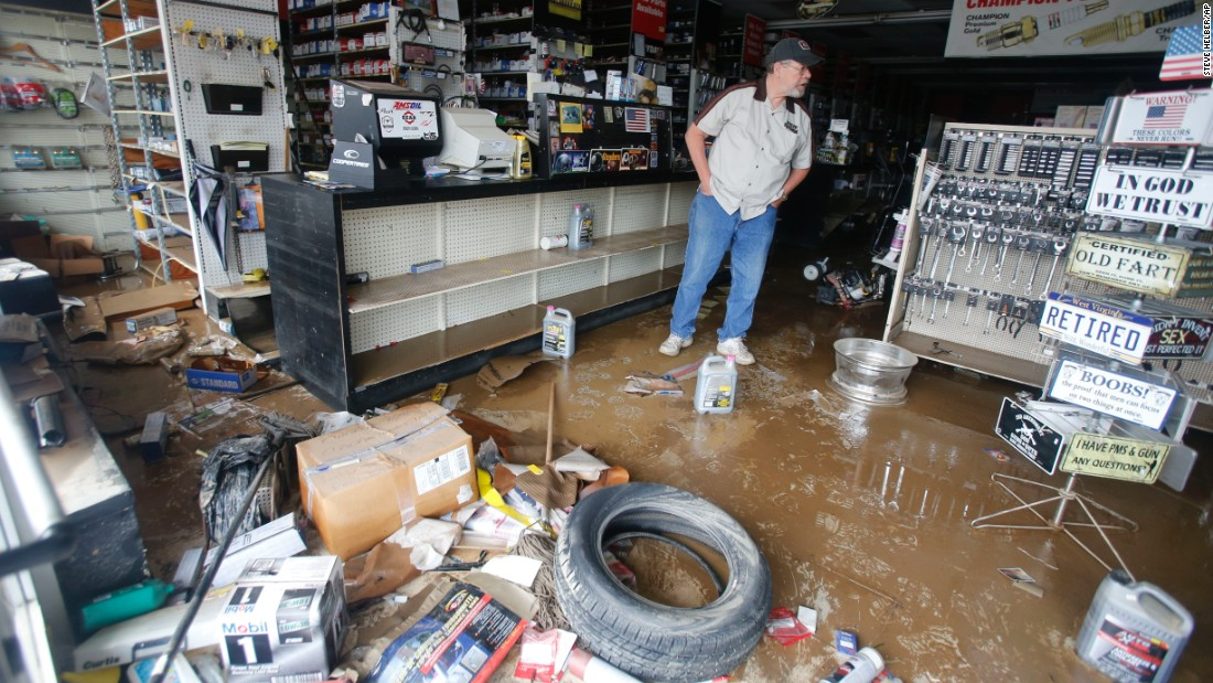Paul Raines looks over his flooded Western Auto store in Rainelle on June 25.