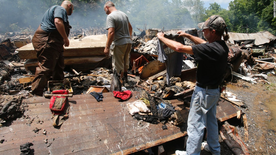 Ron Scott recovers a shirt from the remnants of his home after it was swept off its foundation and burned in White Sulphur Springs, West Virginia, on June 24.