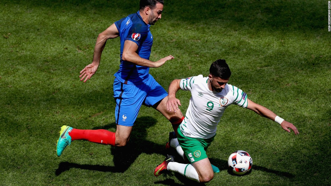 Adil Rami of France fouls Shane Long of Ireland, resulting in a yellow card.