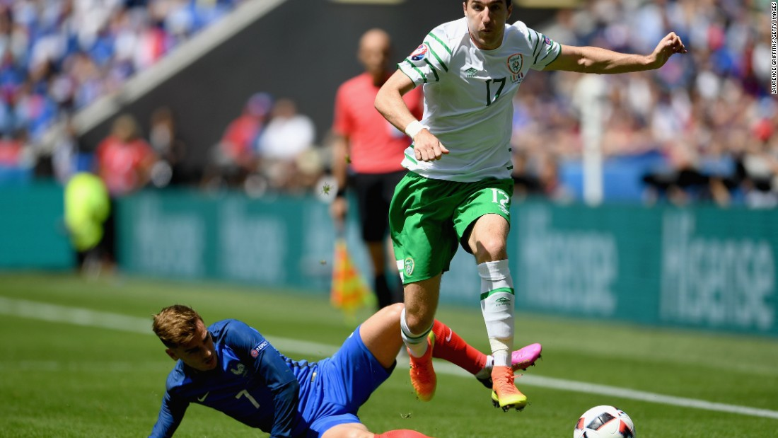 Stephen Ward of Ireland is tackled by Antoine Griezmann of France.