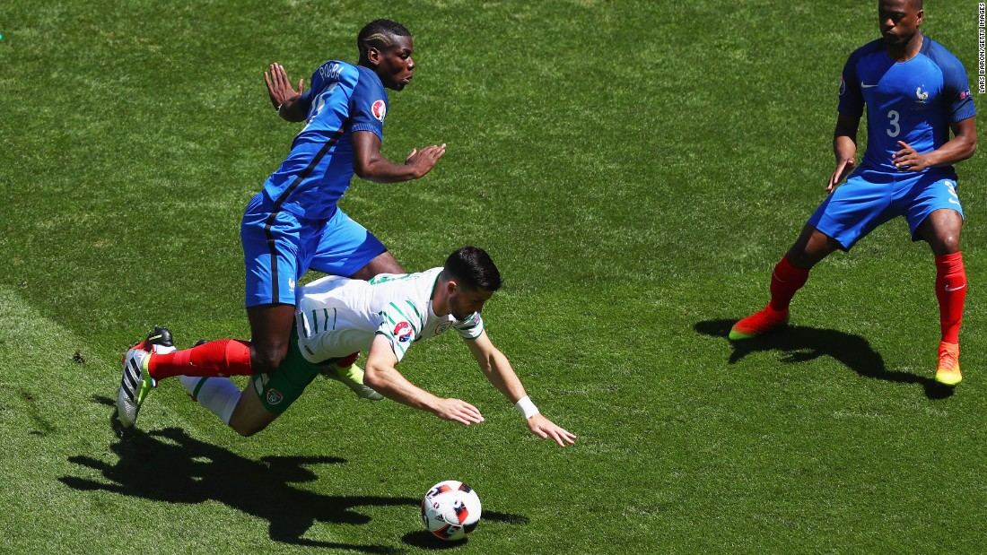 Shane Long of Ireland is challenged by Paul Pogba of France.