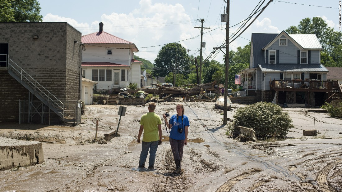 "People survey a mud-covered street after the floodwaters of the Elk River receded in Clendenin, West Virginia, on Saturday, June 25. <a href=""http://www.cnn.com/2016/06/24/us/gallery/west-virginia-flooding/index.html"" target=""_blank"">Fast-moving floodwaters</a> killed at least 24 people in the state."