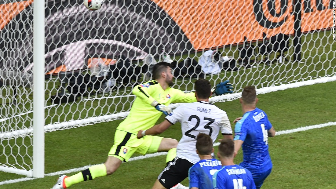 Germany's forward Mario Gomez, center, scores against Slovakia's goalkeeper Matus Kozacik.