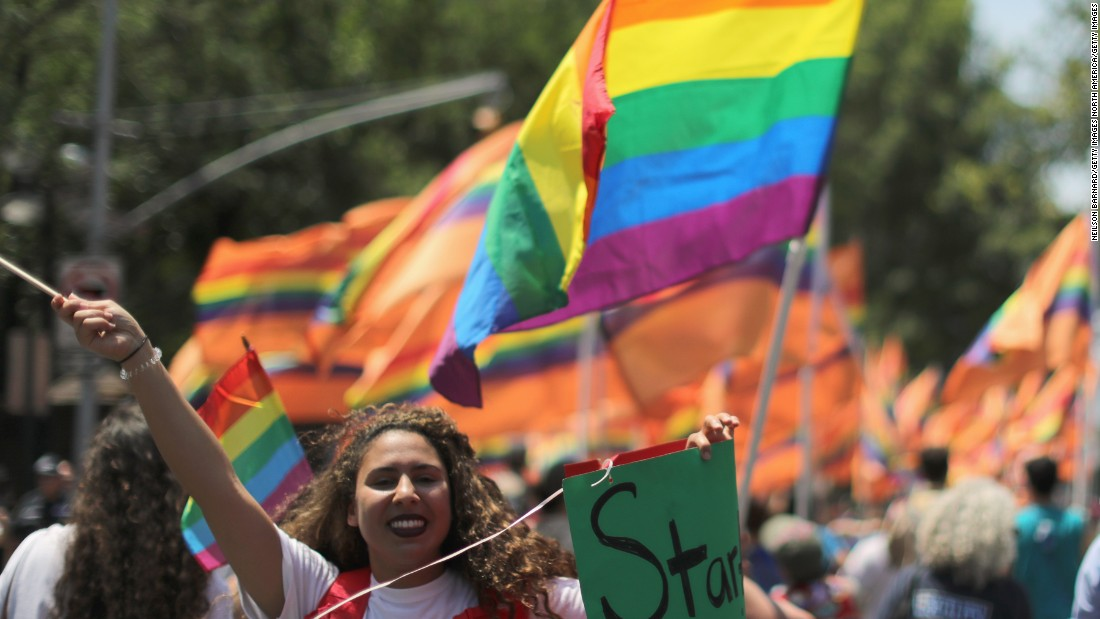 Marchers carry rainbow flags and signs in tribute to the Orlando shooting victims during New York's parade on June 26.
