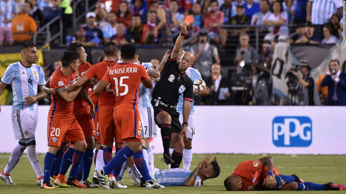 Brazilian referee Heber Lopes red-cards Argentina's Marcos Rojo, center on the ground,  for fouling Chile's Arturo Vidal, right on the ground.