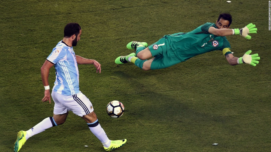 Argentina's Gonzalo Higuain, left,  prepares to shoot against Chile's goalie Claudio Bravo.
