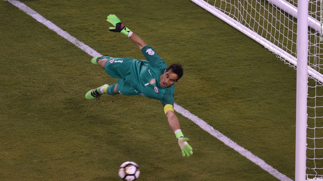 Chile's goalie Claudio Bravo fails to stop a shot by Argentina's Sergio Aguero, out of frame, during the penalty shoot-out.