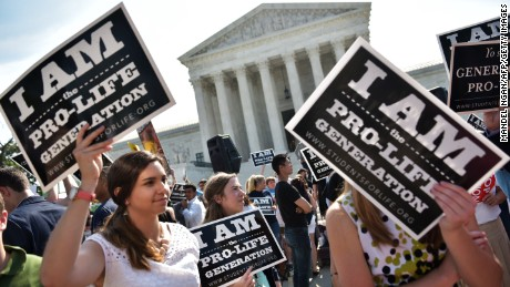 Anti-abortion activists hold placards before a US Supreme Court ruling on a Texas law placing restrictions on abortion clinics, outside of the Supreme Court on June 27, 2016 in Washington, DC. In a case with far-reaching implications for millions of women across the United States, the court ruled 5-3 to strike down measures which activists say have forced more than half of Texas's abortion clinics to close.