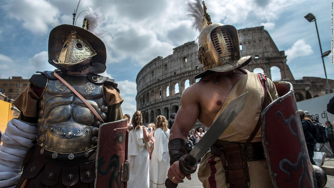 Actors dressed as ancient Roman soldiers stand near the Coliseum in eighth place Rome.