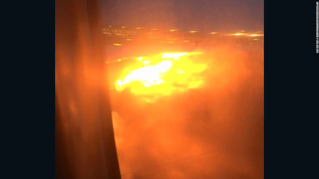 A cell phone photo shot by passenger Lee Bee Yee (facebook.com/premiummall.sg) shows the wing of a Singapore Airlines flight on fire upon landing at Changi Airport on June 27, 2016.