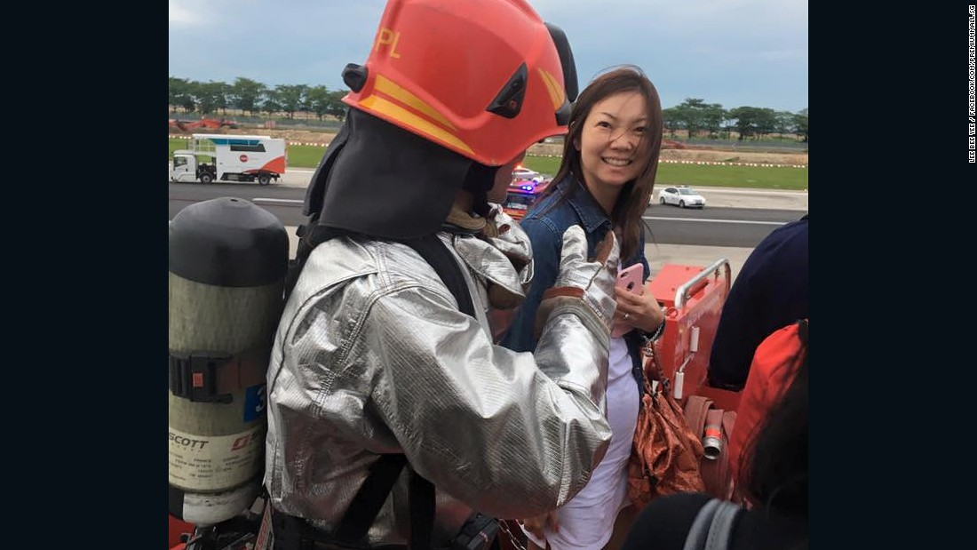 Lee thanks a firefighter as she disembarks the plane.