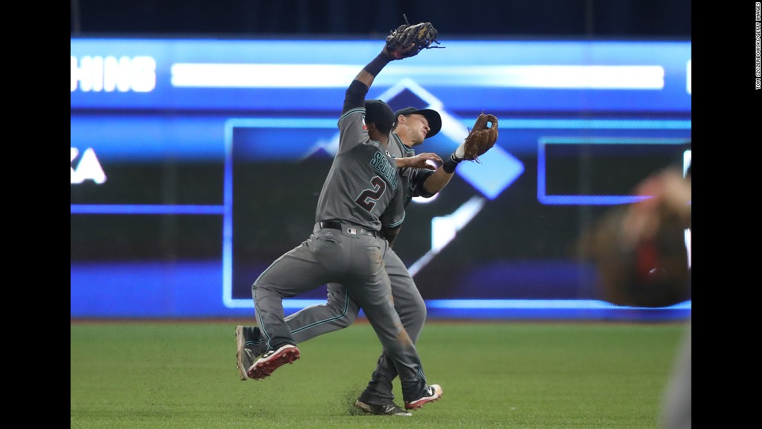 Arizona's Jean Segura nearly collides with teammate Nick Ahmed as he catches a pop fly in Toronto on Tuesday, June 21.