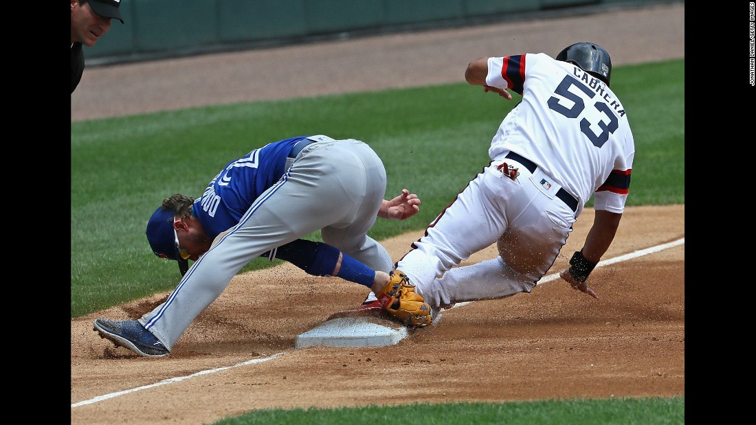 Melky Cabrera of the Chicago White Sox appears to slide safely into third as Josh Donaldson tries to make a tag on Sunday, June 26.