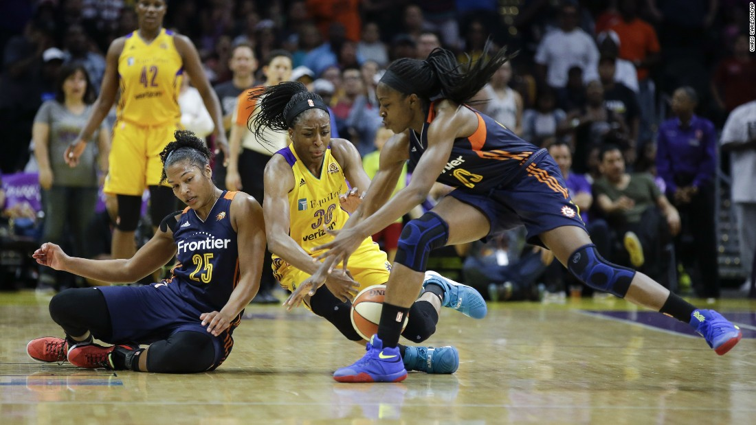 Connecticut's Alyssa Thomas, left, and Chiney Ogwumike try to keep a loose ball away from Nneka Ogwumike during a WNBA game in Los Angeles on Sunday, June 26. Chiney and Nneka are sisters.