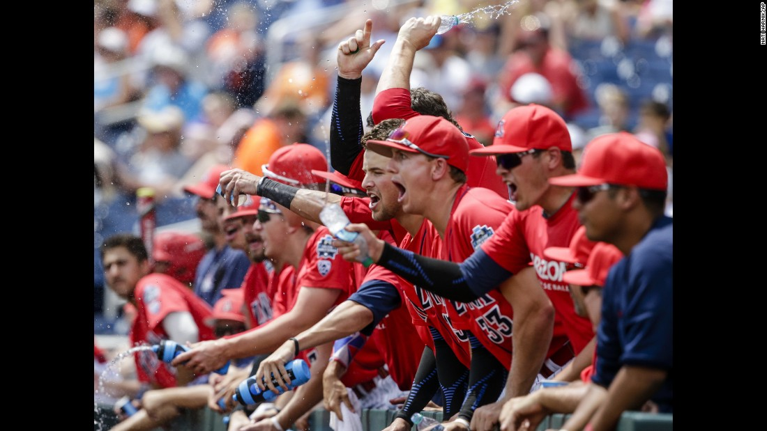 Arizona players celebrate in the dugout after Kyle Lewis scored a run against Oklahoma State during a College World Series game on Saturday, June 25.
