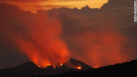 As seen from a hilltop 6 miles away, lava passing through vents within Pu'u O'o cone light the pre-dawn sky on January 22,2004. Lava from Kilauea Volcano near Volcano, Hawai'i has been erupting from Pu'u O'o for over 21 years.