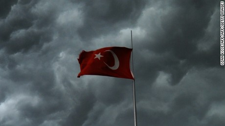 Clouds gather over the Bosphorus behind a Turkish flag during a storm on August 7, 2014, in Istanbul. AFP PHOTO/OZAN KOSE        (Photo credit should read OZAN KOSE/AFP/Getty Images)