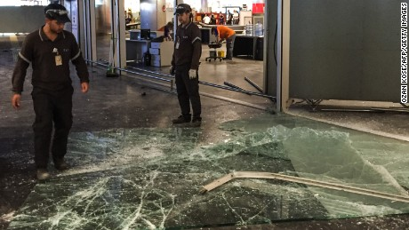 Authorized personnel clear glass debris in Ataturk airport's International arrival terminal on Wednesday, June 29.