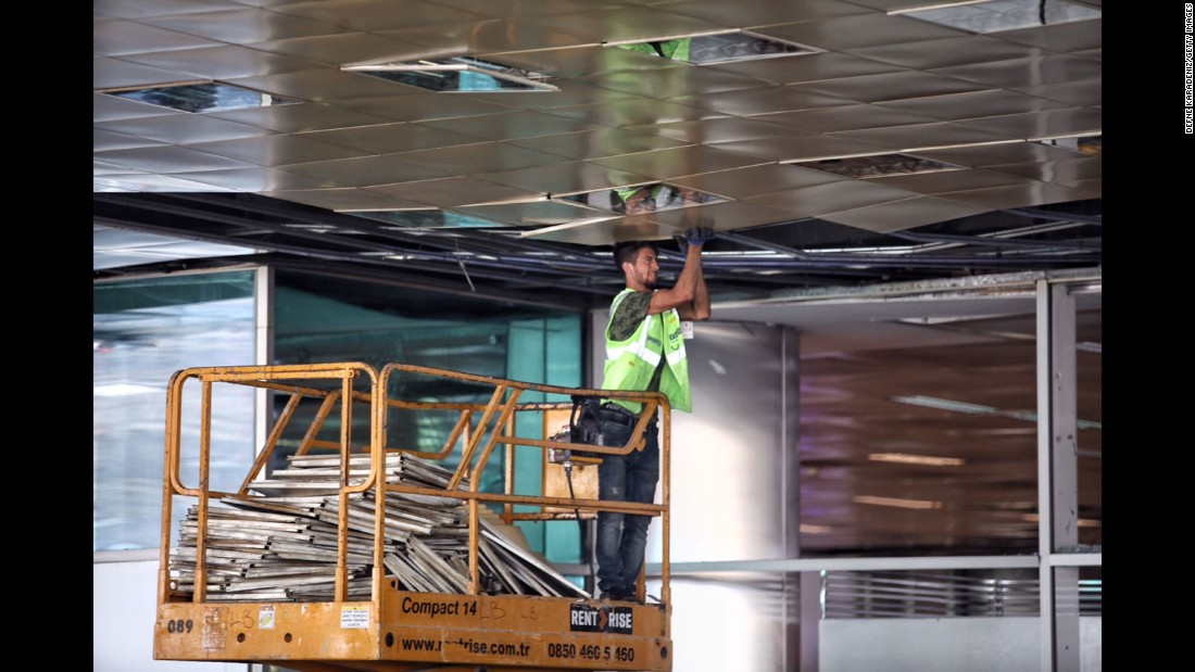 A worker repairs the airport's damaged ceiling on June 29.