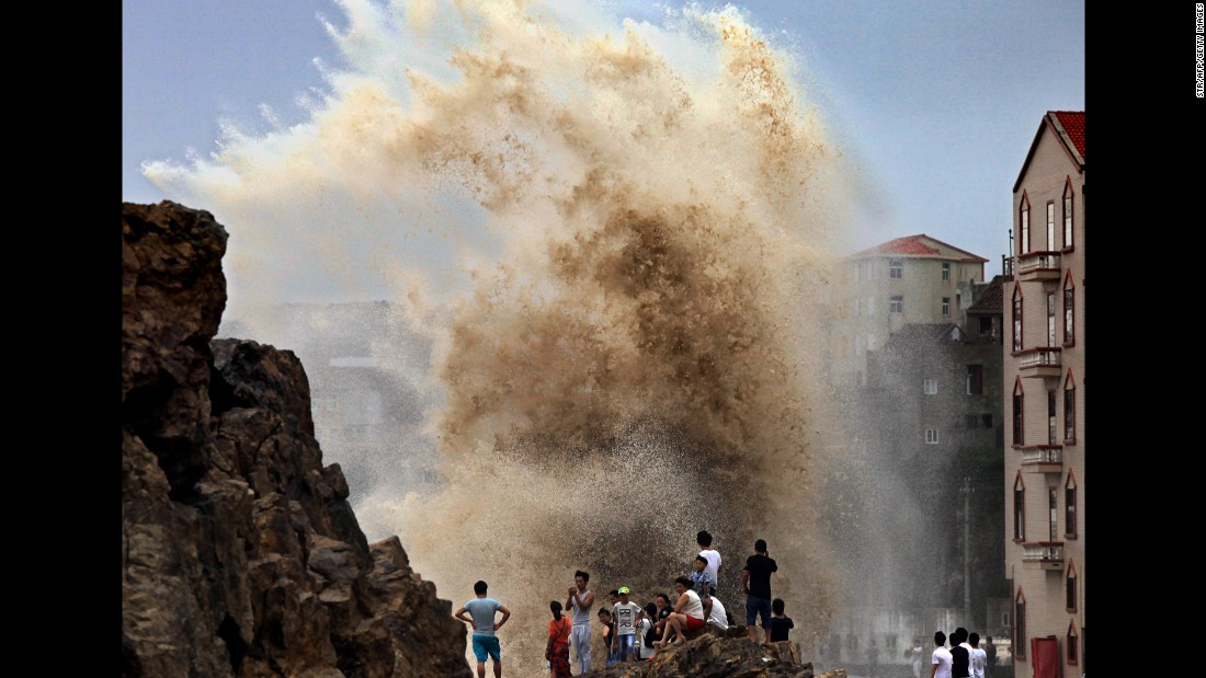 Residents of Wenling, China gather to see huge waves stirred up by strong wind as Typhoon Soudelor draws near in 2015.