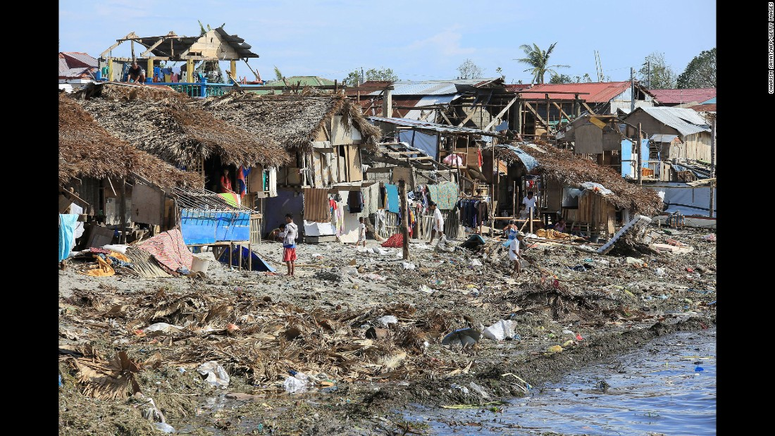 Residents stand next to their damaged houses with blown out roofs after typhoon Melor hit Bulan town, Sorsogon province, south of Manila on December 15, 2015. Tattered lanterns, festive lights and tin roofs littered towns in the central Philippines on December 15 after Typhoon Melor swept through, killing at least four people and leaving millions without power ahead of Christmas.