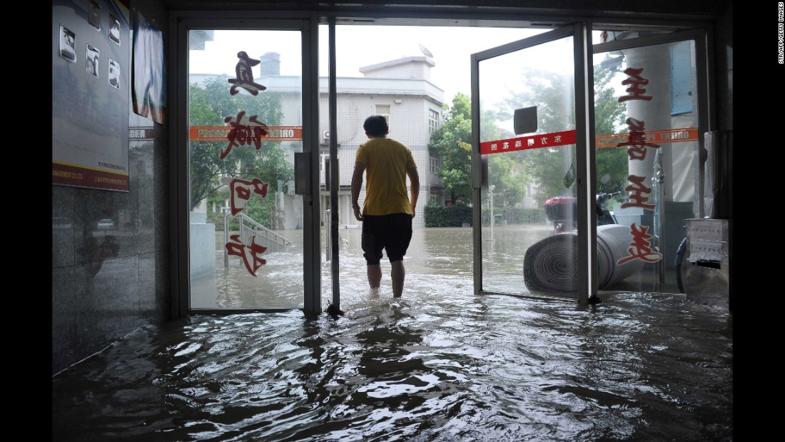 A man walks out through the doors of a flooded building after strong rains hit Shanghai on August 24, 2015. Heavy rains brought by a cold front and enhanced by passing Typhoon Goni brought flooding to many districts across Shanghai.