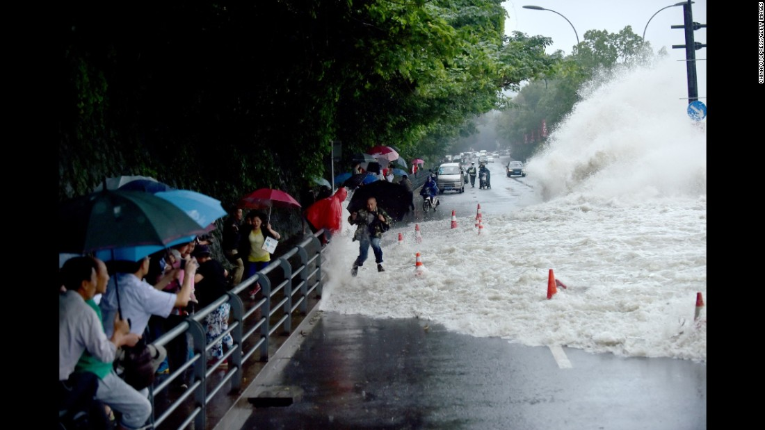 Spectators are swept by huge waves brought by Typhoon Dujuan while watching tides of Qiantang River at a dike on September 29, 2015 in Hangzhou, China.