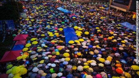 HONG KONG - OCTOBER 28: Umbrellas are opened as tens of thousands come to the main protest site one month after the Hong Kong police used tear gas to disperse protesters October 28, 2014 in Hong Kong, Hong Kong. A peaceful safe atmosphere remains at the massive protest site as artists freely express themselves and families bring their children to experience the Umbrella Revolution.  (Photo by Paula Bronstein/Getty Images)