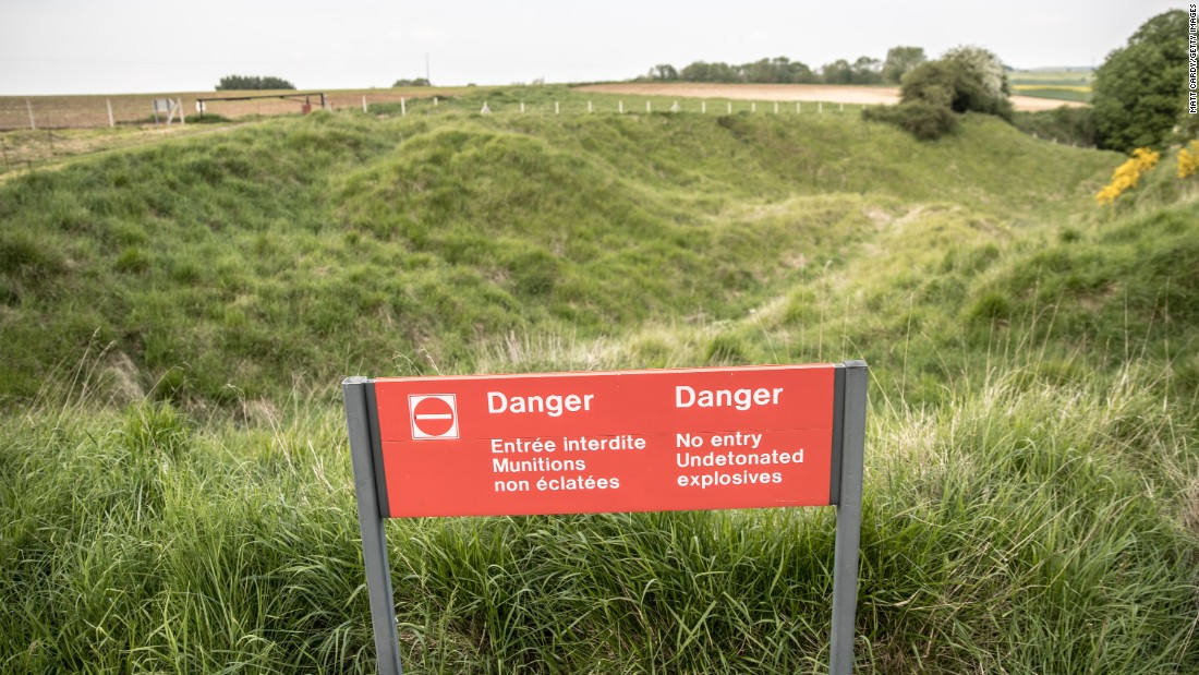 A sign marks the hidden dangers of undetonated explosives where the outline of trenches can still be seen at Newfoundland Memorial Park in Beaumont-Hamel, France.