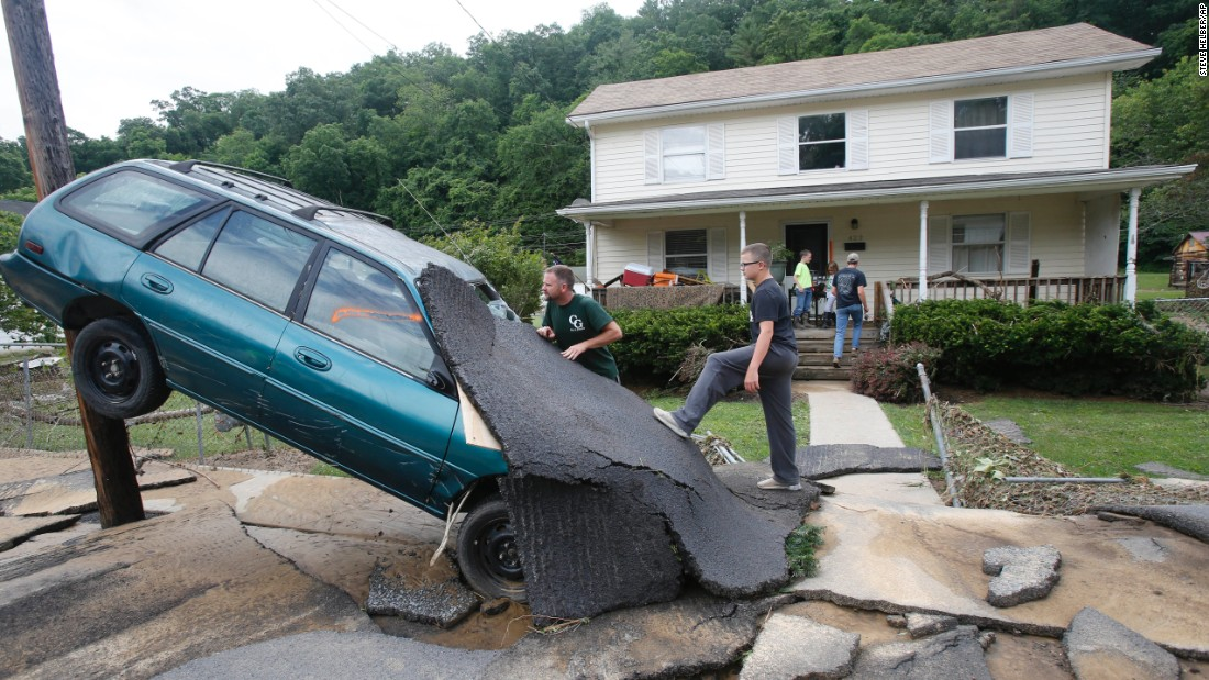 "Jay Bennett, left, and his stepson Easton Phillips survey damage in front of their home in White Sulphur Springs, West Virginia, on Friday, June 24. <a href=""http://www.cnn.com/2016/06/24/us/gallery/west-virginia-flooding/index.html"" target=""_blank"">Deadly floodwaters</a> have wreaked havoc across several counties."