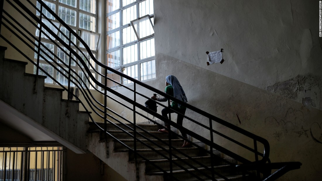 A young Syrian girl climbs the stairs of an abandoned school in Athens, Greece, on Monday, June 27. The school is being used to host refugee families from Syria and Afghanistan.
