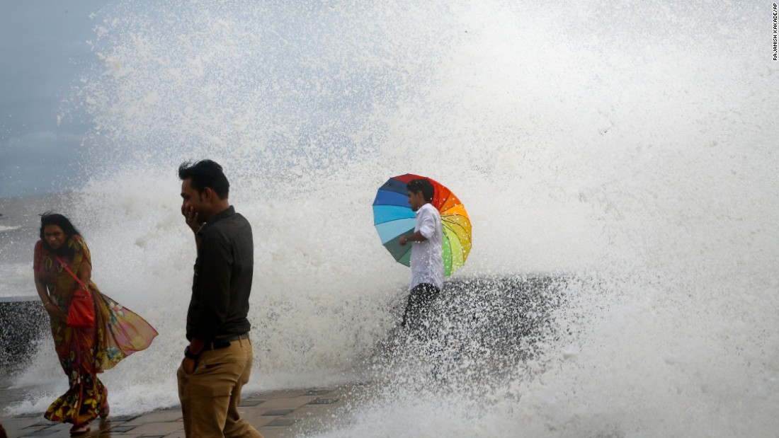 A man holds an umbrella as he enjoys the high-tide waves in Mumbai, India, on Wednesday, June 29.