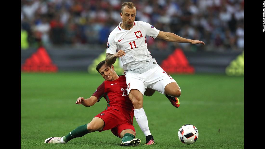 Portugal's Cedric Soares tackles Poland's Kamil Grosicki.