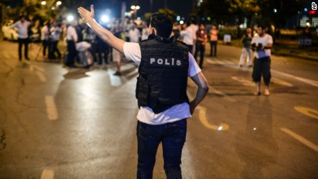 A police officer guides people outside Istanbul's Ataturk airport, Tuesday, June 28, 2016. Two explosions have rocked Istanbul's Ataturk airport, killing several people and wounding others, Turkey's justice minister and another official said Tuesday. A Turkish official says two attackers have blown themselves up at the airport after police fired at them. The official said the attackers detonated the explosives at the entrance of the international terminal before entering the x-ray security check. Turkish authorities have banned distribution of images relating to the Ataturk airport attack within Turkey. (AP Photo) TURKEY OUT