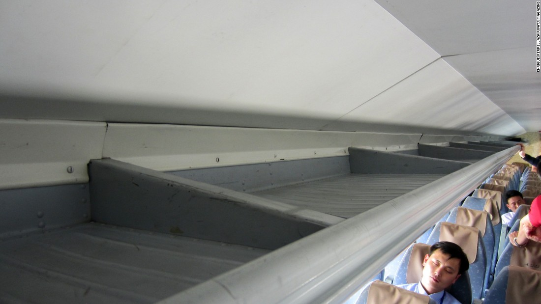 Despite its loud engines, some passengers were able to catch some sleep during the flight. Note the basic design of the plane's overhead storage bins.
