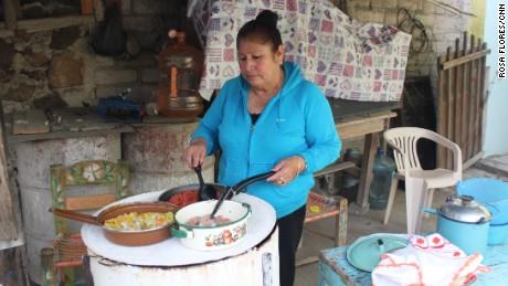 Martha Mendoza cooks on her makeshift firewood stove.