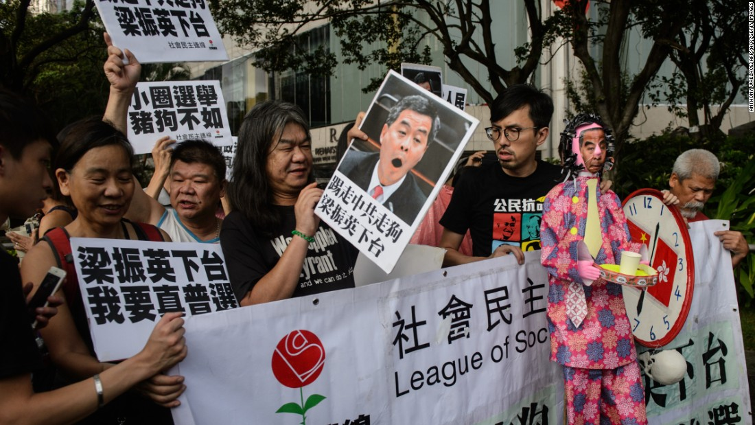 Protesters hold signs ahead of a mass march through central Hong Kong on Friday, July 1, 2016.