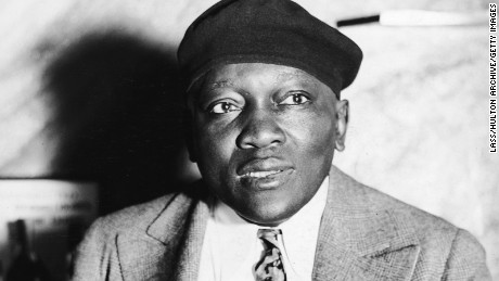 Portrait of American boxer, heavyweight champion and inventor Jack Johnson (1878 - 1946) smoking a cigar, circa 1930s.